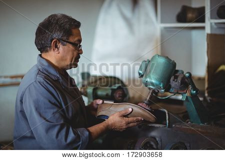 Shoemaker polishing a shoe with machine in workshop