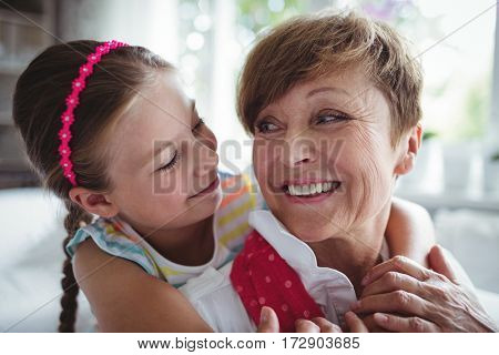 Granddaughter embracing her grandmother at home