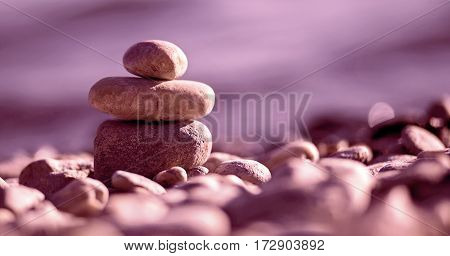 Website banner of Zen balancing pebbles on the beach in purple