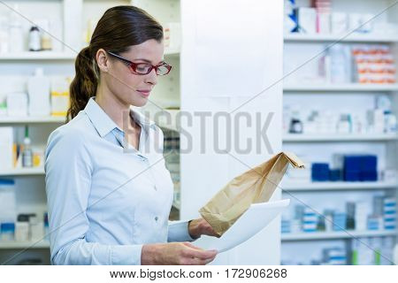 Pharmacist checking prescription and medicine package in pharmacy