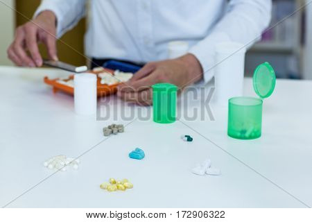 Mid-section of pharmacist putting pill in container at pharmacy