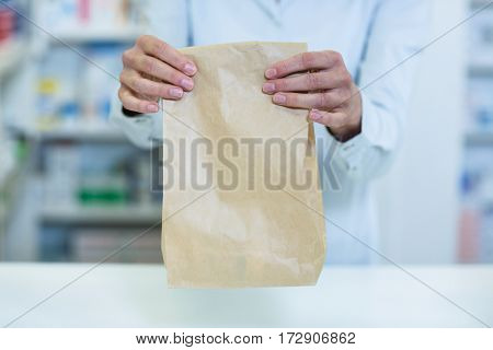 Mid-section of pharmacist holding a medicine package in pharmacy