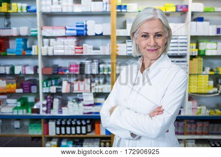 Portrait of pharmacist standing with arms crossed in pharmacy