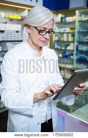 Pharmacist using a digital tablet in pharmacy