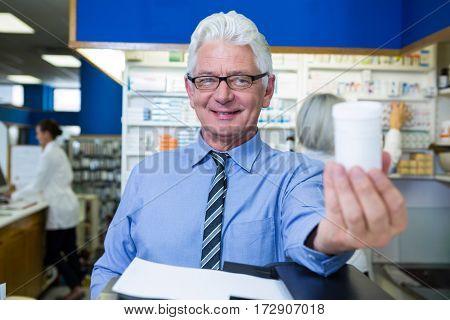 Pharmacist holding a bottle of drug in pharmacy