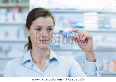 Pharmacist checking a capsule in pharmacy