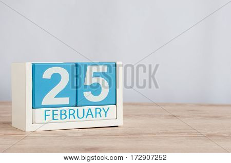February 25th. Day 25 of month, calendar on wooden background. Winter concept. Empty space for text.