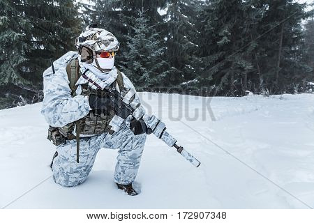 Winter arctic mountains warfare. Action in cold conditions. Trooper with weapons in forest somewhere above the Arctic Circle on one knee