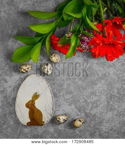 Easter card. On gray concrete background wooden eggs with the Easter bunny quail eggs. Easter bouquet of chrysanthemum. Top view from above and copy space.