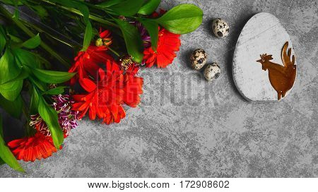 Easter card. On gray concrete background wooden eggs with the rooster quail eggs. Easter bouquet of chrysanthemum. Top view from above and copy space.