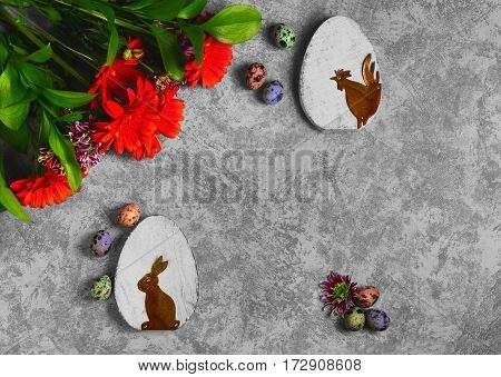Easter card. On gray concrete background Two wooden eggs with the Easter bunny and rooster quail eggs. Easter bouquet of chrysanthemum. Top view from above and copy space.