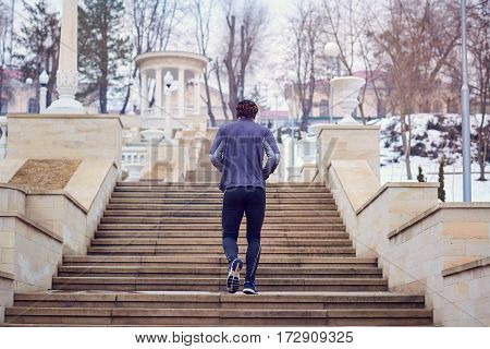 Man in sports clothes running up  stairs  the park. Back view.