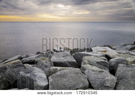 Winter evening view of the harbour rocky breakwater of Camogli, along the shores of Ligurian Sea (Northern Italy). Color image