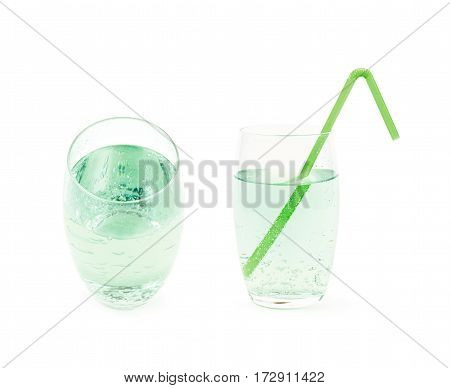 Tall glass filled with the carbonated green lemonade water and served with a drinking straw, composition isolated over the white background, set of two different foreshortenings