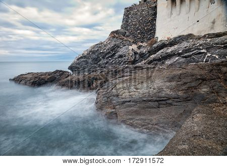 Winter evening view of the sea rocks of Camogli, along the shores of Ligurian Sea (Northern Italy), near the breakwater of the own bay. Color image.