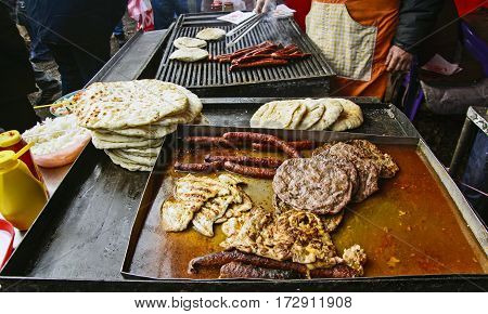 Preparing grill for customers who are waiting.