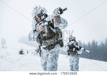 Winter arctic mountains warfare. Action in cold conditions. Pair of special forces weapons in forest somewhere above the Arctic Circle, low angle view