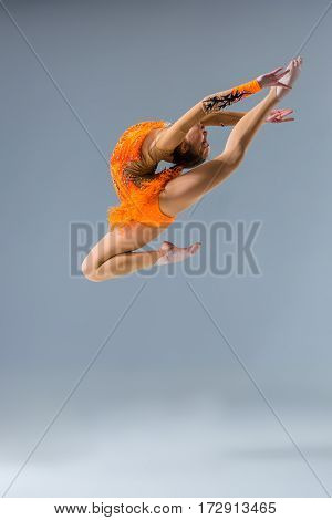 Young slim gymnast in studio. jump. Gymnast on a blue background