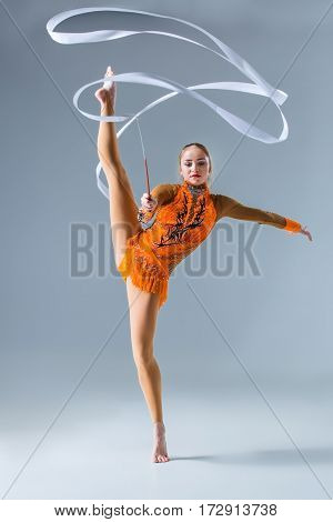 Young gymnast on a white background. Sporting exercises with ribbon. Aerobics. Flexibility. Plastic study. Twine