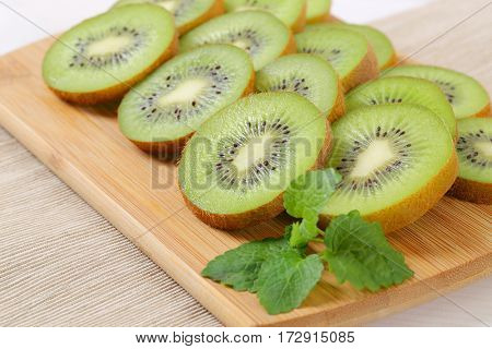 slices of ripe kiwi arranged on wooden cutting board - close up