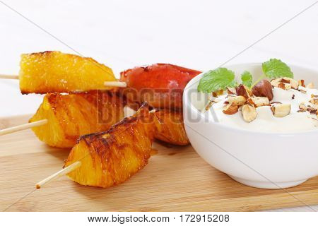 pear and orange skewers with bowl of yogurt, chopped nuts and almonds on wooden cutting board