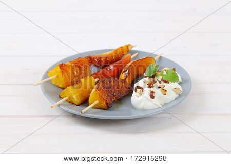 plate of pear and orange skewers with yogurt, chopped nuts and almonds