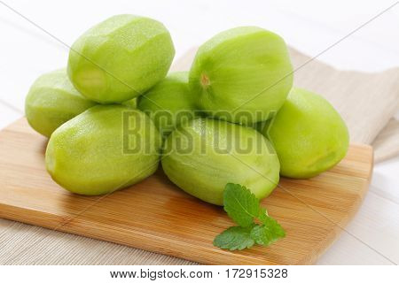 pile of peeled kiwi on wooden cutting board - close up