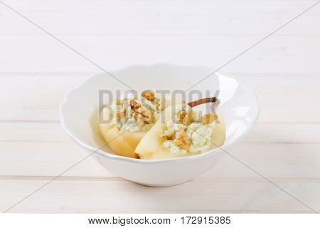 bowl of halved pears with blue cheese and walnuts on white background