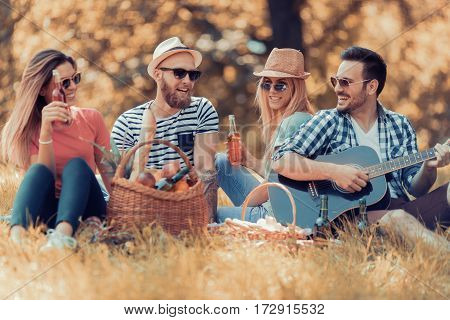 Group of happy friends playing guitar in the park.Travel tourism picnic and people concept.