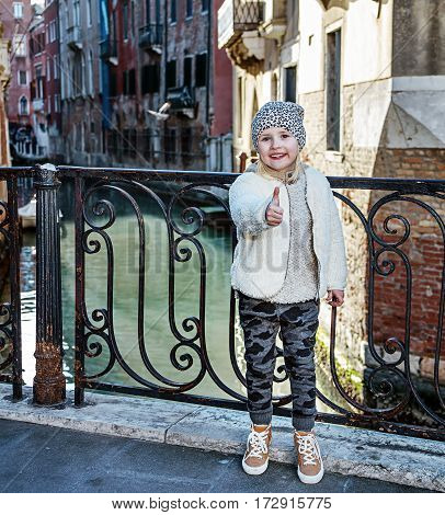 Venice. Off the Beaten Path. Full length portrait of modern child in Venice Italy in the winter showing thumbs up