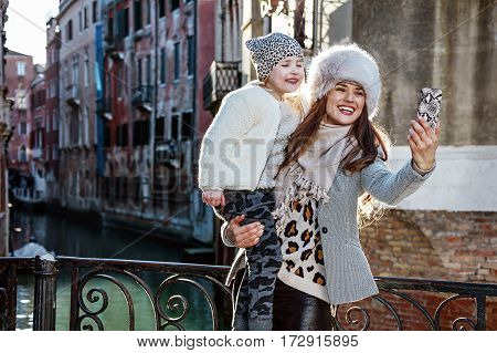 Venice. Off the Beaten Path. happy modern mother and child tourists in Venice Italy in the winter with mobile phone taking selfie