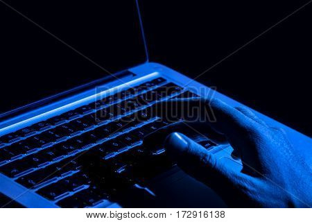 hand on the computer in the dark