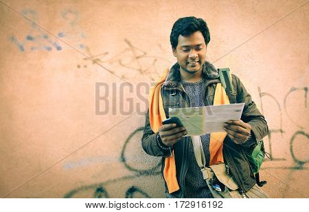Indian tourist man looking map leaning at grunge urban wall background - Travel portrait of young bangladeshi guy searching street on guide casual fall wear - Vintage warm filter