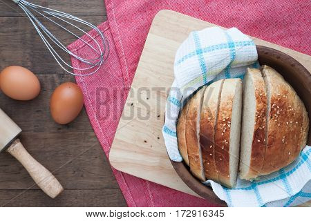 Sliced homemade bread with eggs on wood table with copy space Flat lay