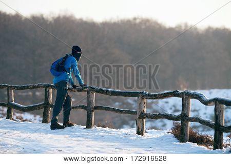 Hiker Resting At Fence Enjoying The Landscape.
