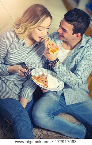 Couple relaxing at home and eating pizza.They are laughing and eating pizza and having a great time.