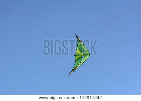 green with yellow kite floating in the blue sky Sunny day