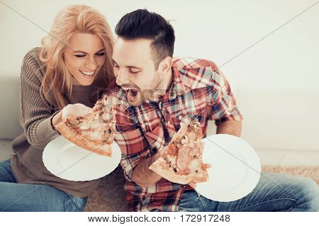 Couple eating pizza snack at home,having fun