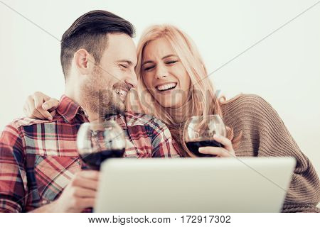 Young couple celebrating with red wine at homeenjoying together at home.Spending nice time at home.