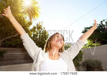 Smiling Older Woman With Arms Outstretched