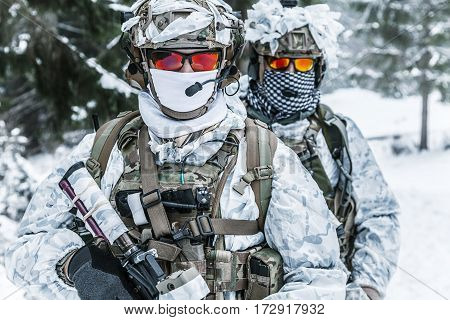 Winter arctic mountains warfare. Action in cold conditions. Soldiers with weapons in forest somewhere above the Arctic Circle
