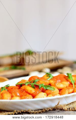 Vegetarian baked beans with carrots, tomatoes and fresh arugula on a plate and on a wooden table. Slow cooked homemade baked beans recipe. Rustic style. Vertical photo