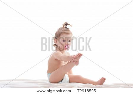 Little cute kid in pampers playing and doing stretching by leg. Little girl sitting on floor at studio, baby sucking baby nipple.
