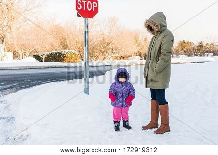 Mother and toddler all rugged up in sub-zero temperatures outdoors in Canada at bus stop