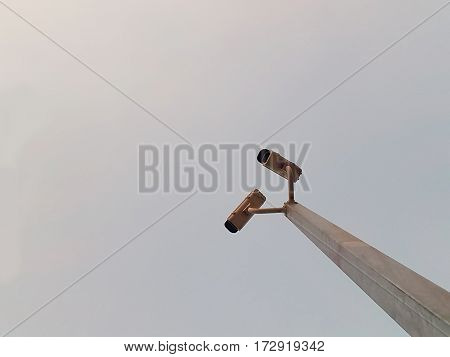 CCTV surveillance security camera equipment in sunset for safety system area control outdoor,Two security cameras against blue sky.