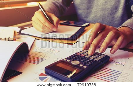 Young Man Using Calculator And Writing Note And Calculate Finance At Home.