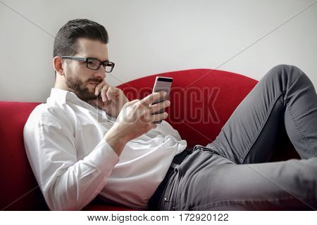 Man on the sofa using a smartphone