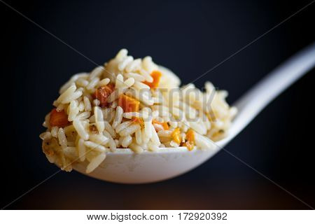 pilaf cooked in a large white spoon on black background