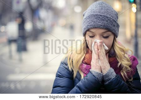 Woman blowing her nose into handkerchief