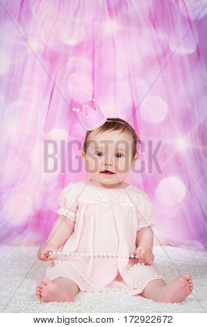 Girl with a crown, sitting on a pink background with bokeh